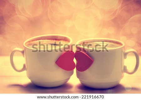 Two coffee cups with red hearts as a kissing lips - stock photo