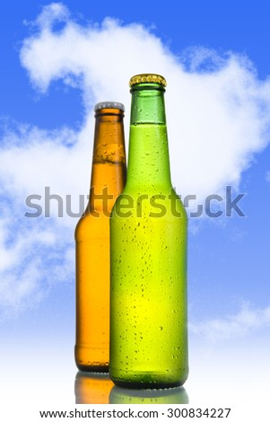 Two Cold frosted beer in green and golden brown bottle frosted and tempting  isolated on a blue sky background in alcoholic refreshing drink concept