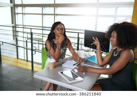 Two  colleages discussing ideas using a tablet and computer - stock photo