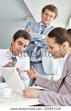 Two colleagues discussing data in laptop  - stock photo