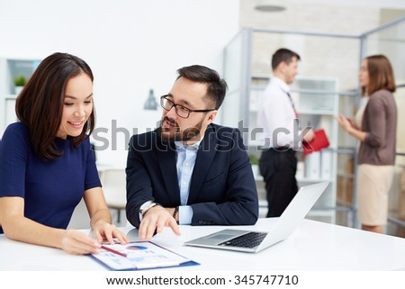 Two colleagues discussing document in working environment in office - stock photo