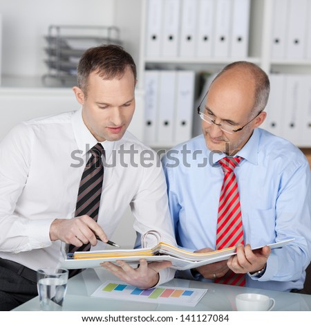 Two colleagues discussing financial plan with consultant at the office - stock photo