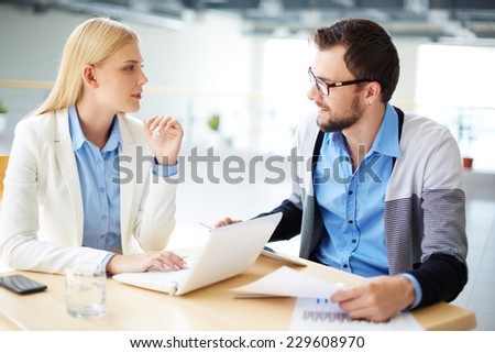Two colleagues discussing ideas or project at meeting  - stock photo