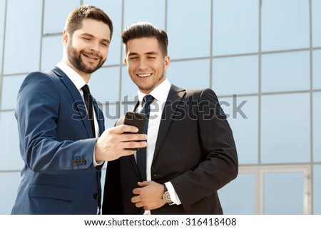 Two colleagues discussing something on a cellphone - stock photo