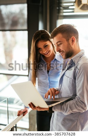 Two colleagues discussing work on a laptop. - stock photo