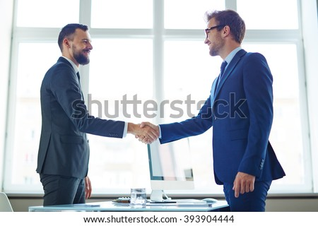 Two colleagues handshaking after meeting - stock photo