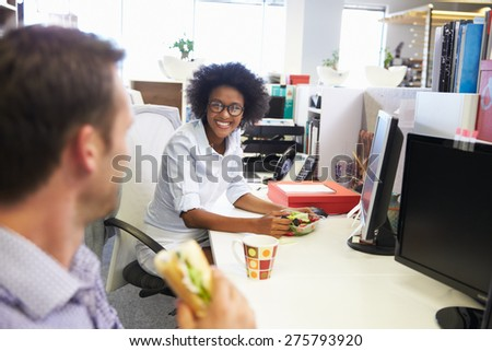 Two colleagues having a lunch break at work - stock photo