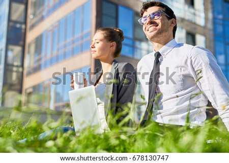Two colleagues having break outdoors on sunny day