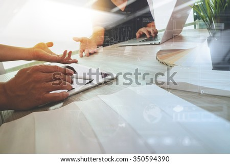 two colleagues interior designers discussing data with blank screen new modern computer laptop and pro digital tablet with sample material on wooden desk as concept