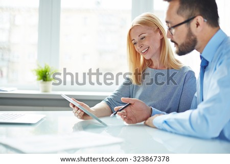 Two colleagues looking at data in touchpad while businessman giving explanations - stock photo