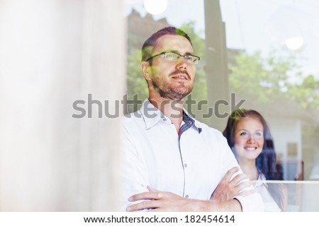 two colleagues looking through the window in office - stock photo