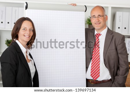 two colleagues standing next to white flipchart in office - stock photo