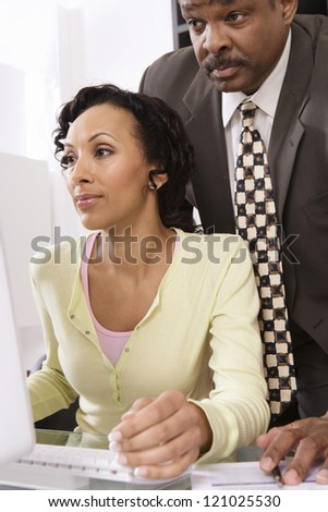 Two colleagues watching computer screen at office - stock photo