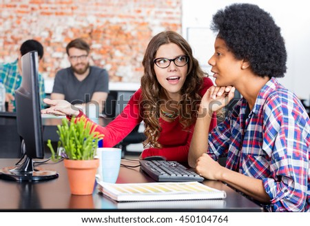 Two colleagues woman talking discussing sitting office desk computer business people working casual wear - stock photo