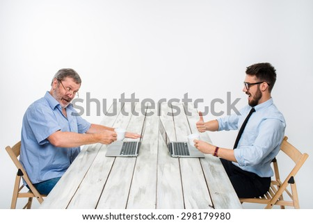 two colleagues working on project together on light gray background. They drinking coffee. happy man and jealous man. the concept of competition in the business - stock photo