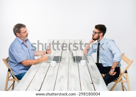 two colleagues working on project together on light gray background. They drinking coffee. happy man and jealous man. the concept of competition in the business