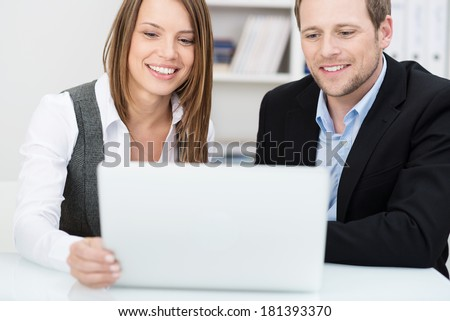 Two colleagues working together in the office with a smiling friendly young man and woman sitting sharing a laptop computer as they have a discussion - stock photo