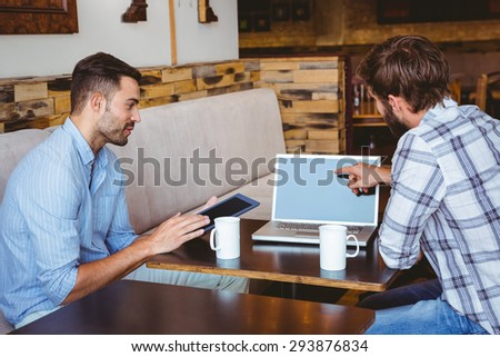 two colleagues working with laptop and tablet at the cafe - stock photo