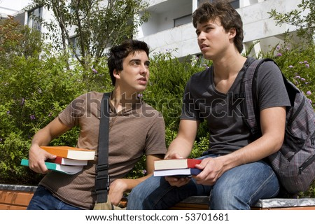 Two college or university students speaking and smiling - stock photo