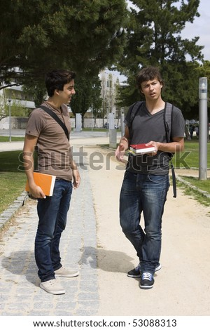 Two college or university students walking on a park path