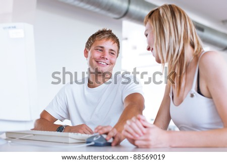 two college students having fun studying together, using a computer in a university library/study room (shallow DOF, color toned image) - stock photo