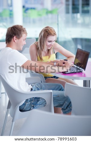 two college students having fun studying together, using a laptop computer (shallow DOF, color toned image)