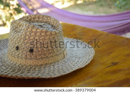 Two-color straw hat on wood table in calm and relaxing atmosphere - stock photo
