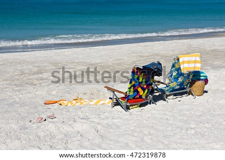 Two Colorful Beach Chairs with Beach Towels and Flip Flops