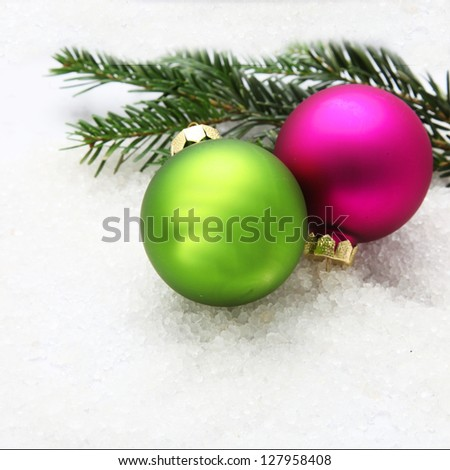 Two colorful Christmas baubles on and pine tree branches on snow - stock photo