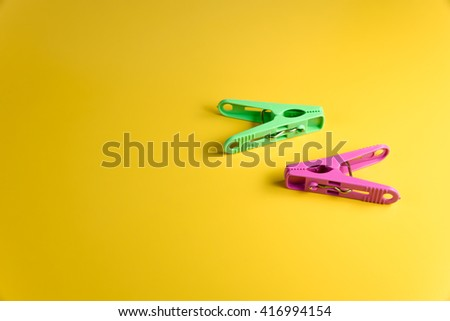 two colorful clothespin green and pink lay on yellow background - stock photo
