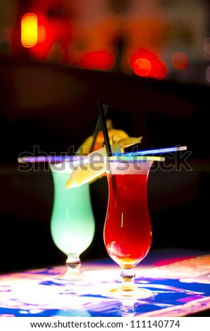 two colorful cocktails on a bar table with blurred background