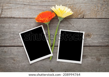 Two colorful gerbera flowers and photo frames on wooden table - stock photo