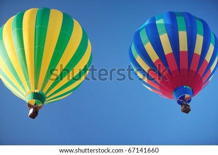 Two colorful hot air balloons floating lazily away on a vibrant blue sky.