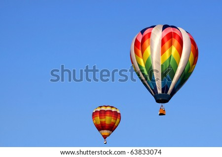 Two colorful hot air balloons in the blue sky