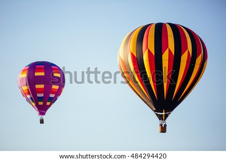 Two colorful hot air balloons isolated against a clear sky