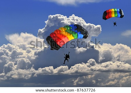 Two colorful parachutes on stormy sky