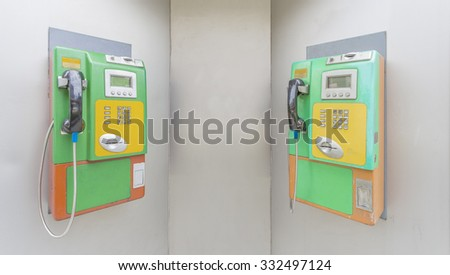 Two colorful public pay phones in phone booth - stock photo