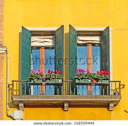 two colorful window in a yellow wall - stock photo