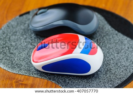 Two computer mouse on a gray mouse pad - stock photo