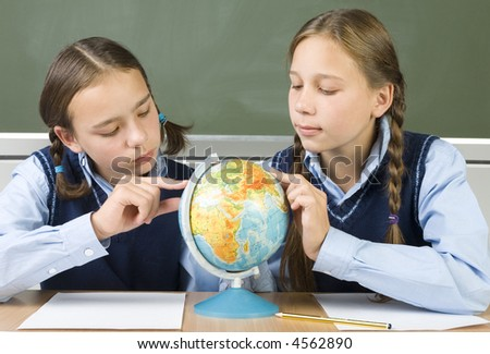 Two concentrated gilrs sitting at desk and searching something at globe. Front view - stock photo