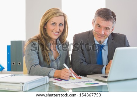 Two concentrated mature business people smiling at camera trying to understand figures at office - stock photo