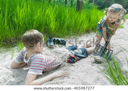 Two concentrated siblings playing on beach dune and burying each other in white sand at pinewood background