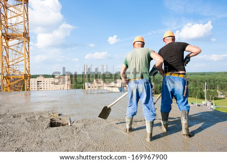 Two concrete workers plasterers levelling liquid cement at construction site - stock photo