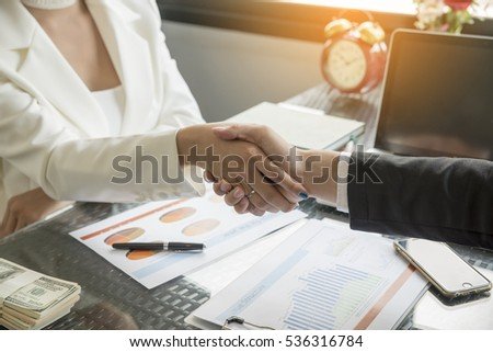 Two confidence businessman and businesswoman shaking hands close-up view of hands,negotiating business.