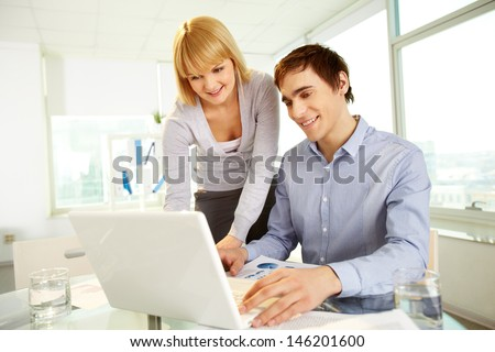 Two confident business partners planning work on laptop