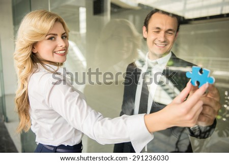 Two confident business people holding together piece of puzzle at office.
