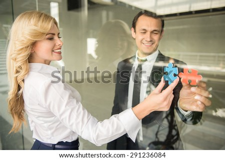 Two confident business people trying to connect small pieces of puzzle at office.