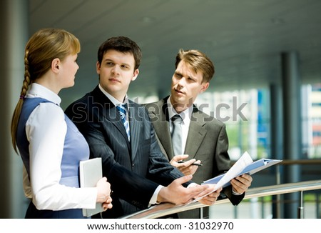 Two confident businessmen looking at pretty specialist sharing her ideas