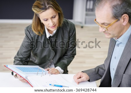 two confident businesspeople a a discussion looking at papers on the desk - stock photo