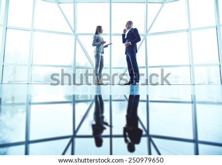 Two confident colleagues interacting in office - stock photo